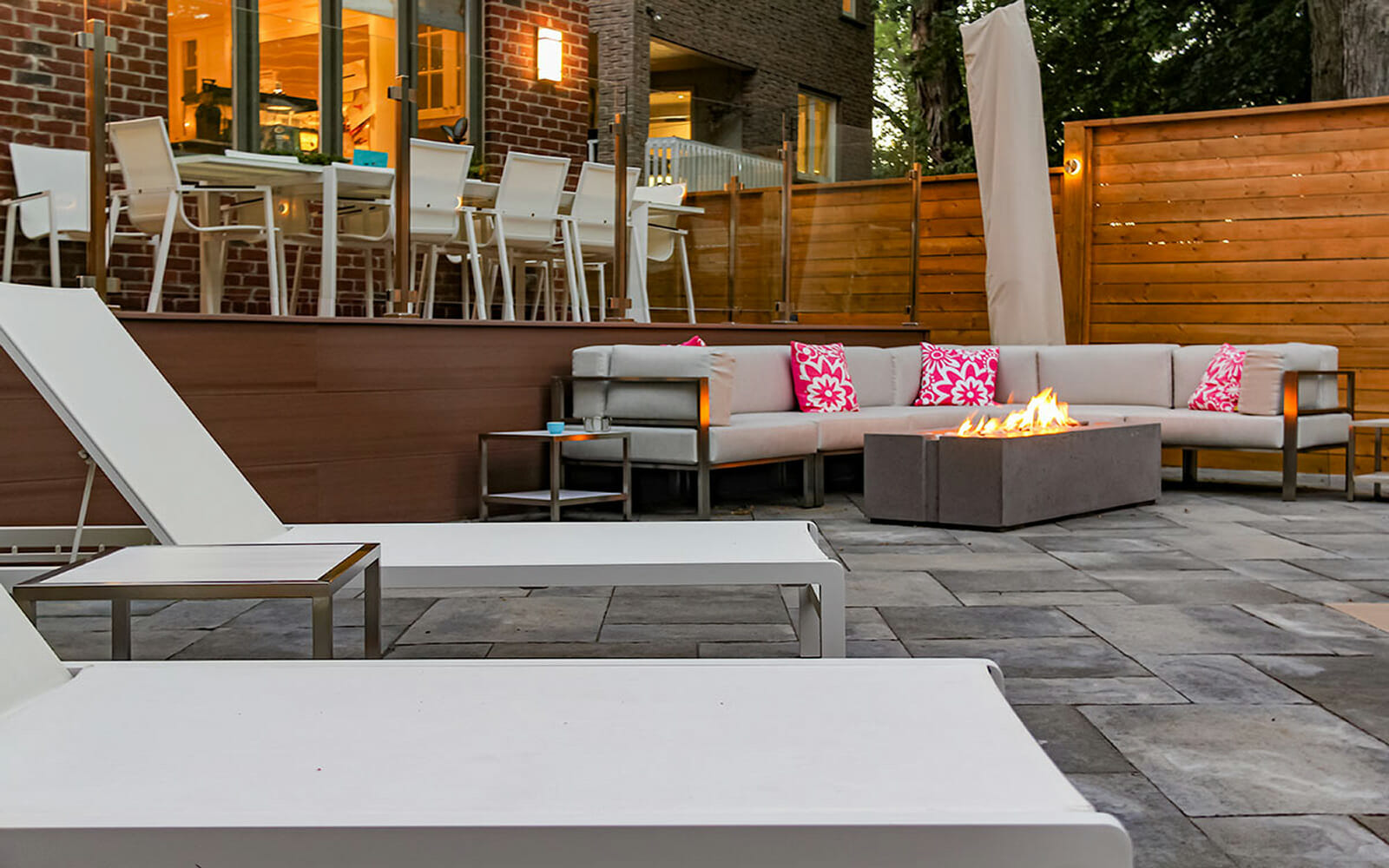 Complete Backyard Toronto Landscaping Design Project; Featuring Outdoor Fireplace, Interlocking & Azek Deck Build with Stainless Steel Glass Railing by The Toronto Landscaping Company.