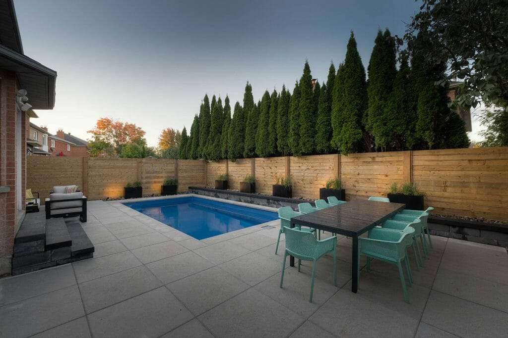 Complete Small Toronto Backyard Landscaping Project with Concrete Pool, Privacy Fence, Outdoor Fireplace, Interlocking & Retaining Wall