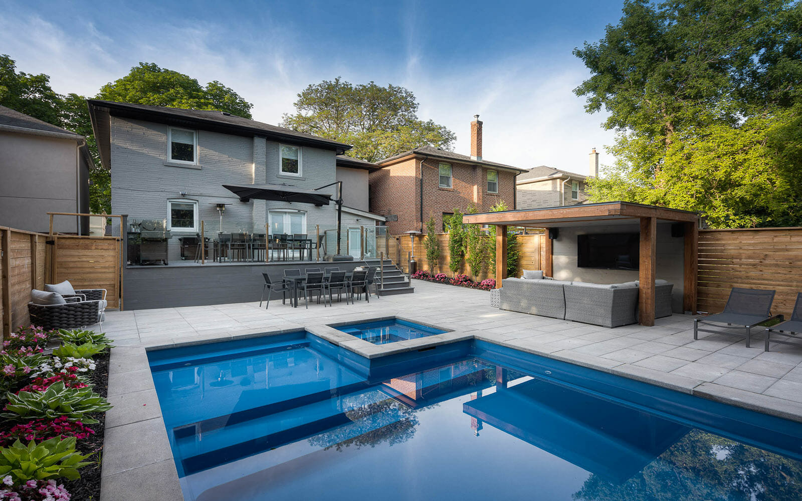 Complete Toronto Landscaping Project; Featuring Composite Decking, Stainless Steel Glass Railings, Fiberglass Pool Installation, Privacy Fence & Woodworking Pergola by Toronto Landscaping Company.