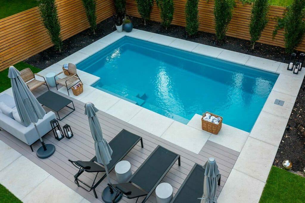 Elegant Toronto Backyard Landscape Design; Featuring FIberglass Pool Installation, Stone Pool Deck Interlocking, Softscape, & PVC Decking by M.E. Contracting