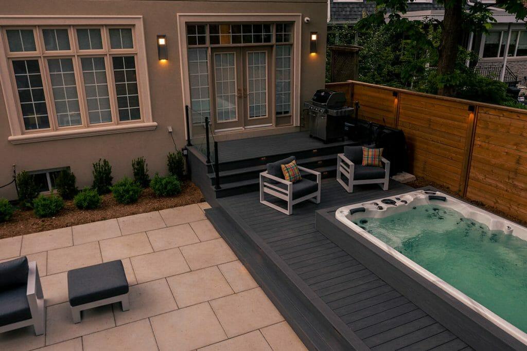 Small Backyard Landscaping Project; Featuring Interlocking, Glass & Aluminum Railings, PVC Decking, Swim Spa, and Patio Design