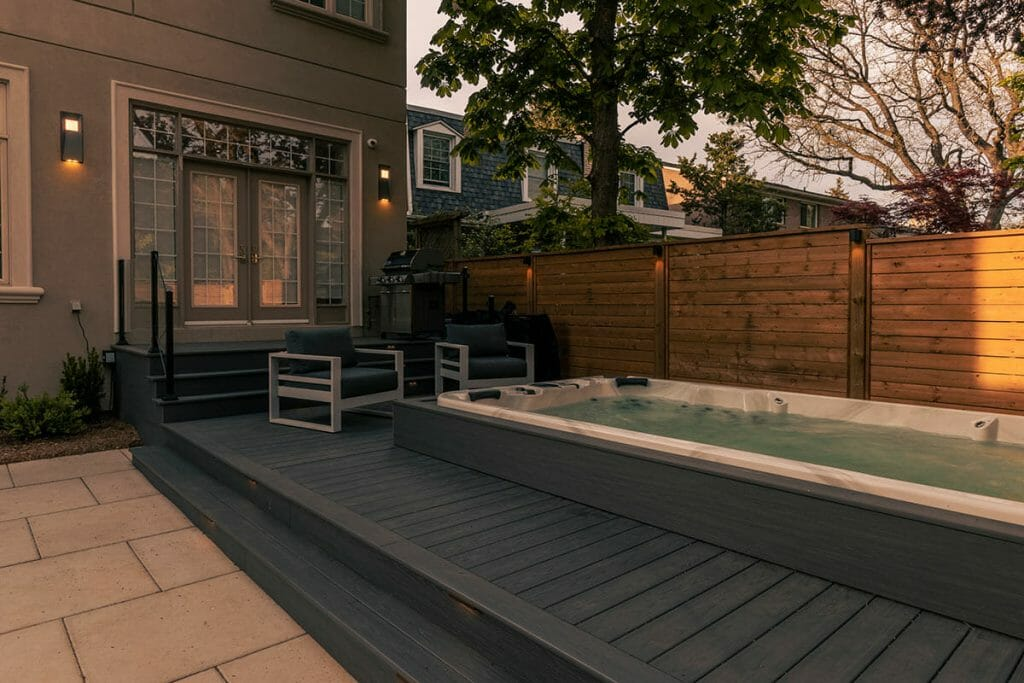 Small Toronto Backyard Landscaping Project; Featuring PVC Decking, Swim Spa Installation, and Interlocking with Lighting by M.E. Contracting