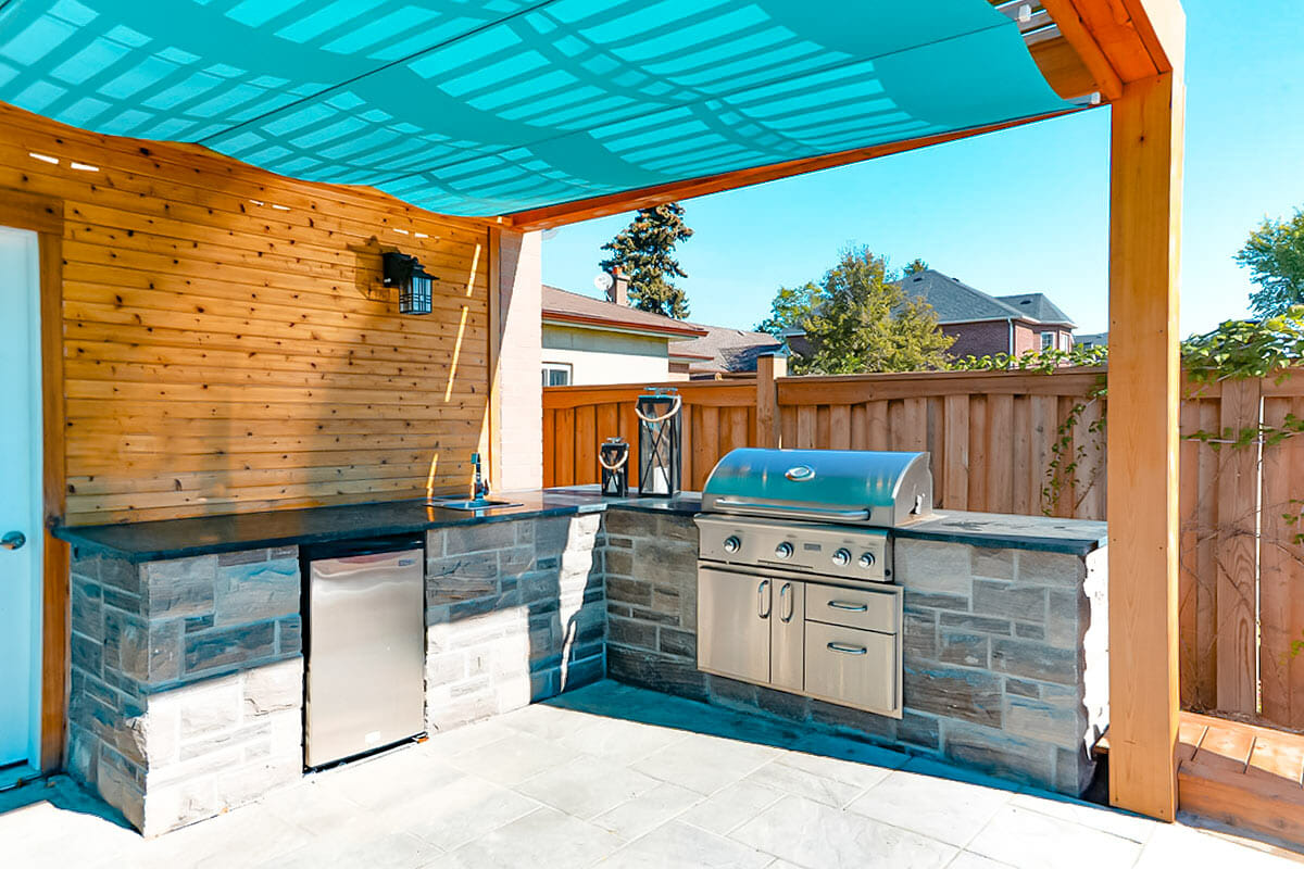 Small Toronto Landscape Design & Pool Construction Project by M.E. Contracting; Featuring Pergola & Outdoor Kitchen.