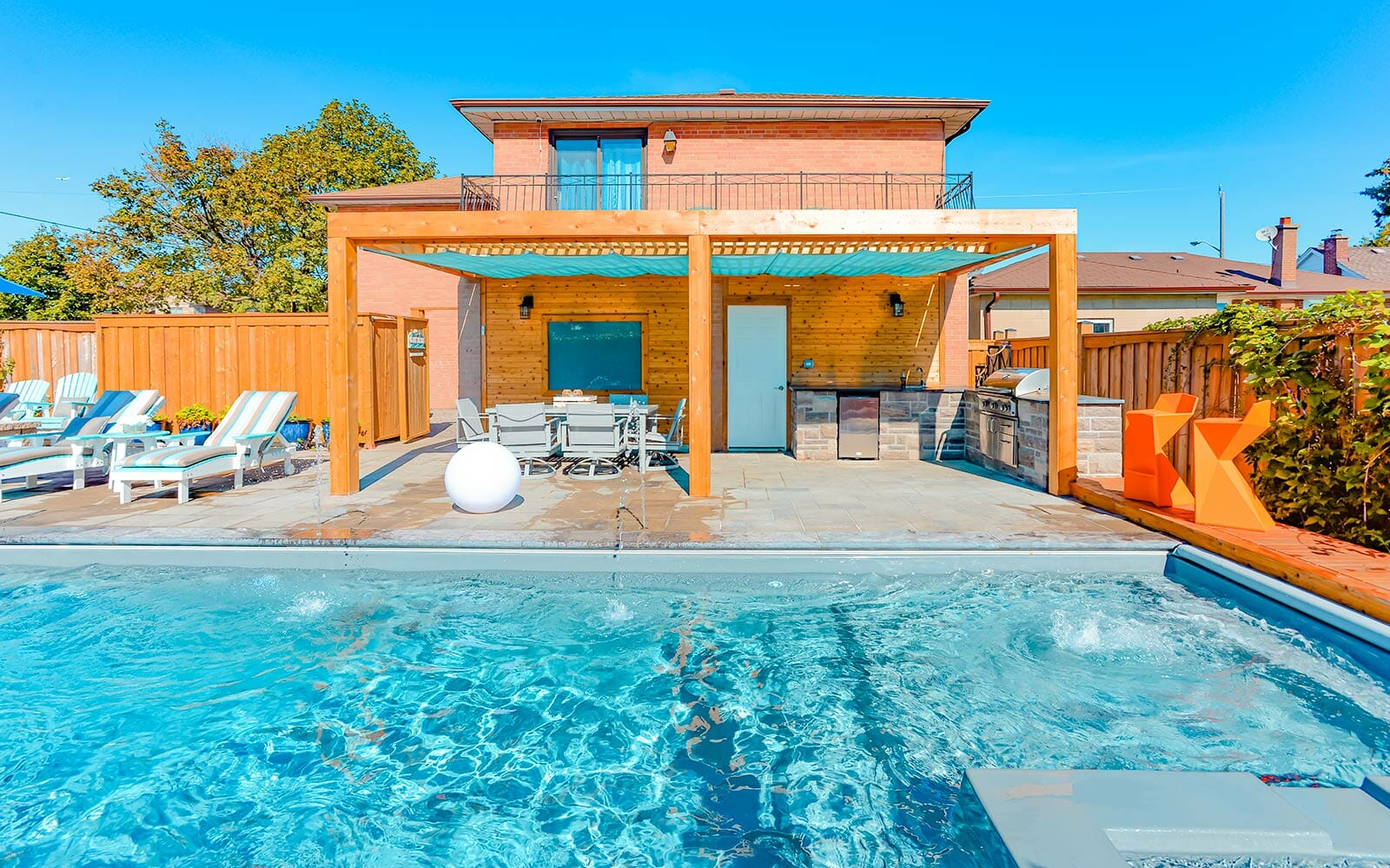 Toronto Landscape Design & Pool Construction Project with Woodworking Pergola, Water Features, Interlocking & Outdoor Firepit by The Toronto Landscaping Company.