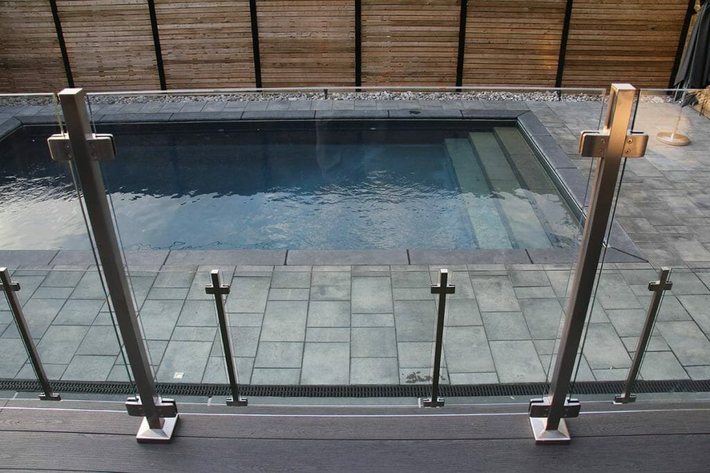 Complete Decking and Railings Project by Toronto Landscaping Company; Featuring Stainless Steel & Glass Railings, Fence Construction, Concrete Pool & Interlocking.