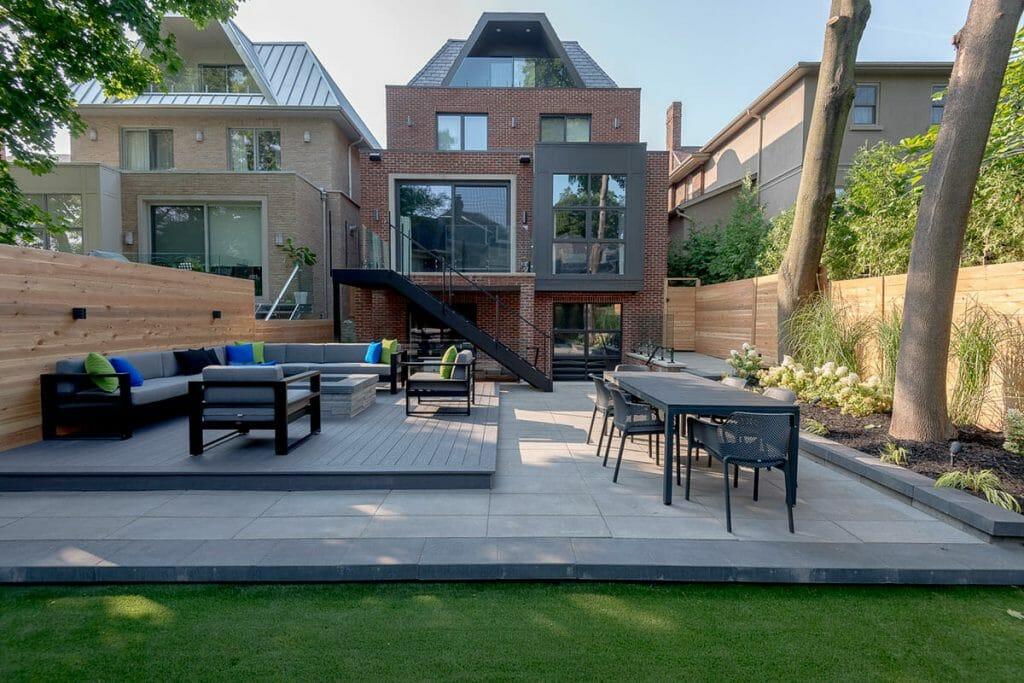 Toronto Landscape Design & Patio Design Project; Featuring Composite Decking, Wrought Iron Glass Railings, Outdoor Fireplace & Interlocking