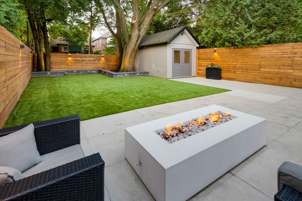 Toronto Landscape Design Project; Featuring Small Retaining Wall, Interlocking, Privacy Fence & Outdoor Fireplace