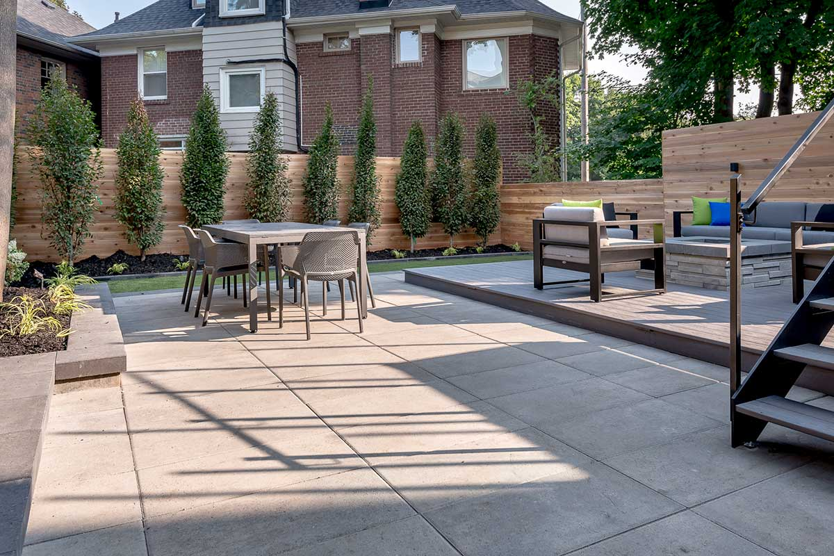 Toronto Landscape Design Project by M.E. Contracting; Featuring Interlocking, Small Retaining Wall, Cedar Privacy Fence, Composite Decking & Outdoor Fireplace