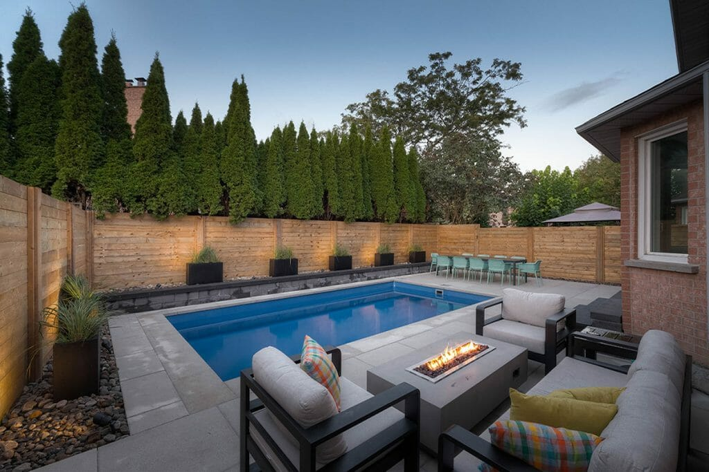 Toronto Landscape Project For Small Backyard; Featuring Outdoor Fireplace, Concrete Pool, Retaining Wall & Privacy Fence