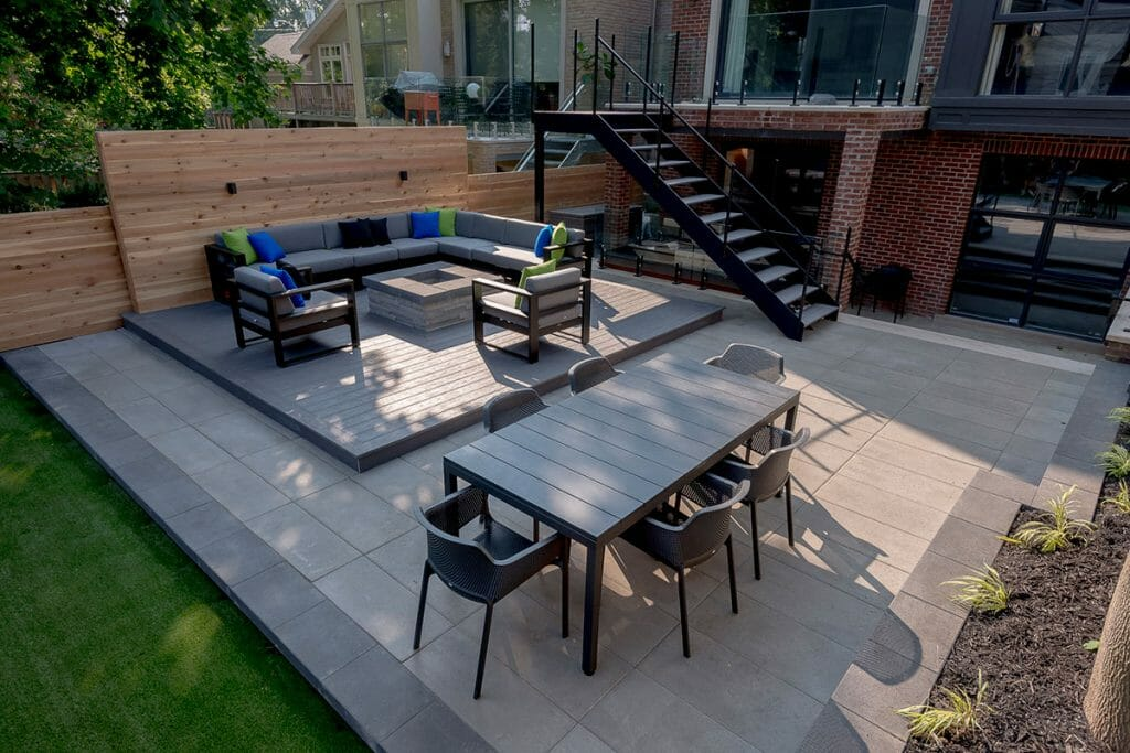 Toronto Landscaping Design Project; Featuring Outdoor Fireplace, Interlocking, Composite Decking, Wrought Iron Railings, Small Retaining Wall & Cedar Privacy Fence