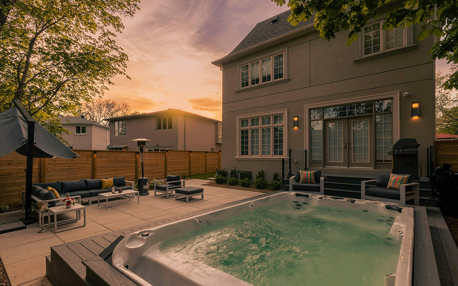 Premium Toronto Landscaping Project; Featuring Swim Spa Installation, PVC Deck with Glass Railings and Outdoor Lighting Features, Patio Stone Interlocking, and Privacy Fence Build by M.E. Contracting.